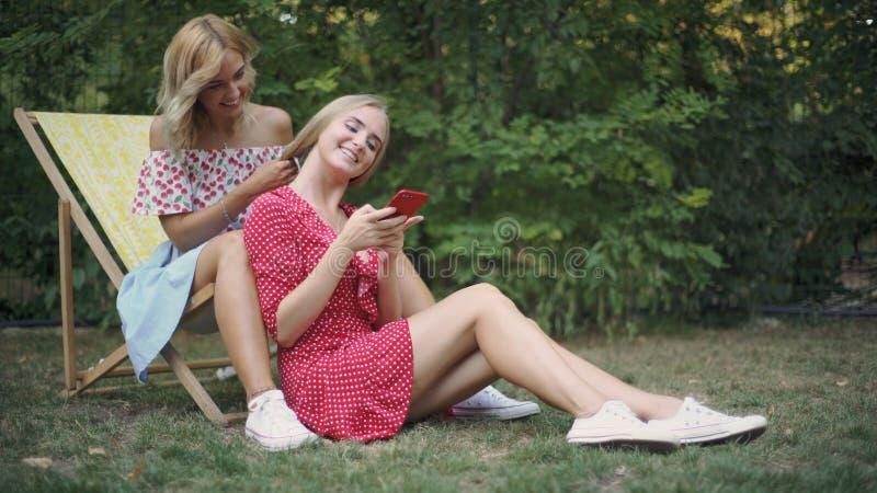 Dos mujeres atractivas jovenes que hablan y que caminan en el parque Hermanas en parque foto de archivo