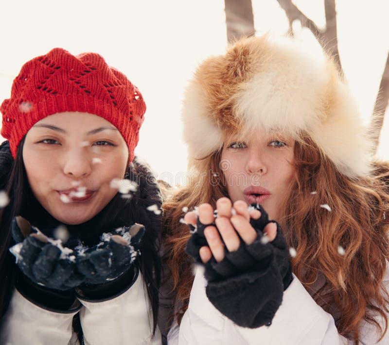 Dos mujeres atractivas que soplan nieve en invierno foto de archivo