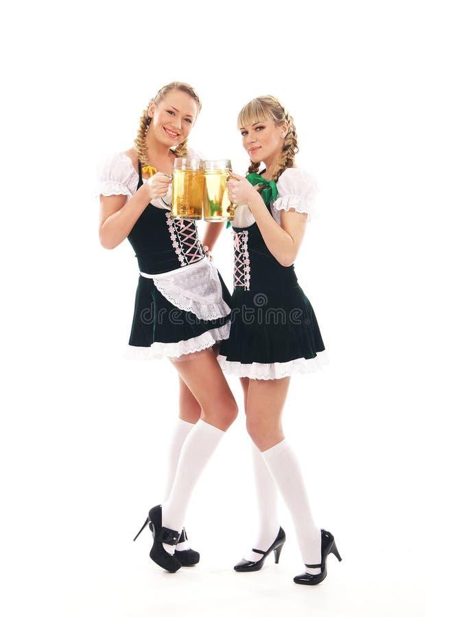 Dos mujeres bávaras caucásicas jovenes con la cerveza fotografía de archivo