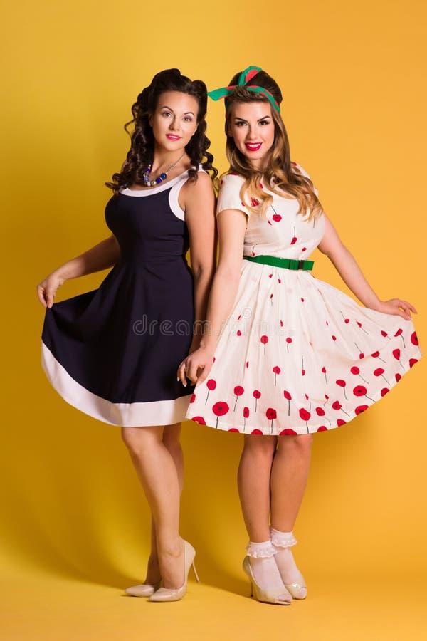 Dos mujeres bonitas en vestidos presentan en el estudio amarillo, perno para arriba fotos de archivo libres de regalías