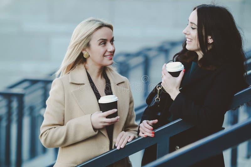 Dos mujeres caminan en la ciudad, caf? de la bebida imagenes de archivo