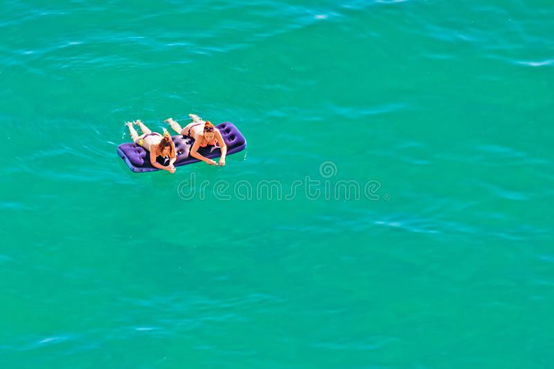 Dos mujeres caucásicas hermosas jovenes en bikini que toman el sol y mentira de relajación en el colchón en el agua azul tranquil fotos de archivo libres de regalías