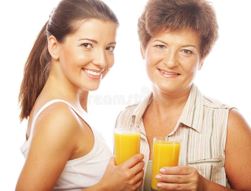 Dos mujeres con el zumo de naranja. fotografía de archivo libre de regalías