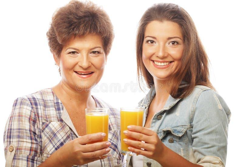 Dos mujeres con el zumo de naranja. fotografía de archivo