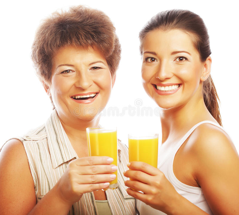 Dos mujeres con el zumo de naranja. imagen de archivo