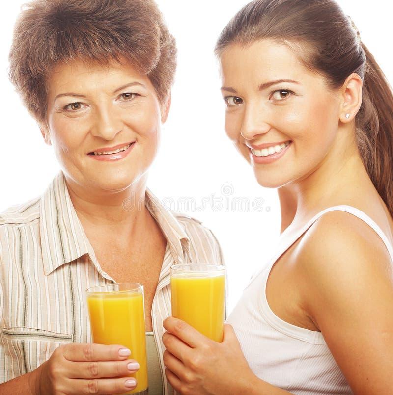 Dos mujeres con el zumo de naranja. foto de archivo libre de regalías