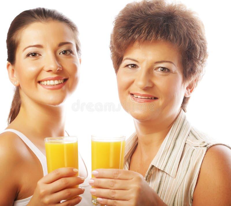 Dos mujeres con el zumo de naranja Madre e hija fotografía de archivo