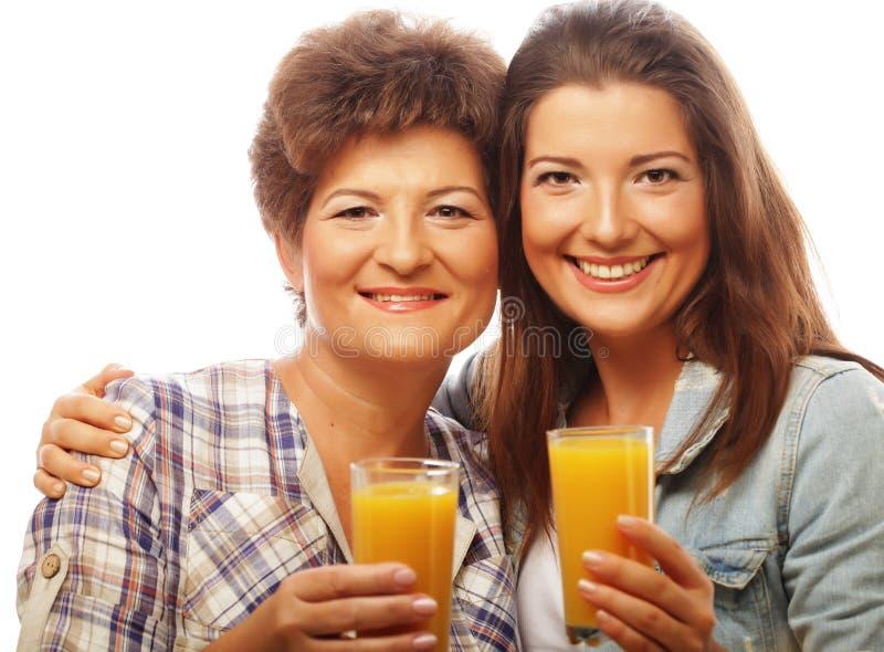 Dos mujeres con el zumo de naranja Madre e hija imágenes de archivo libres de regalías