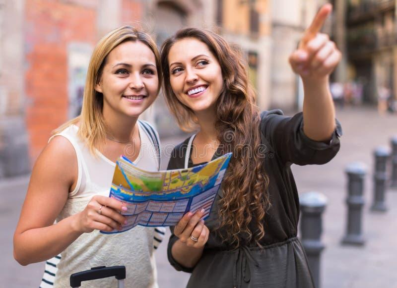 Dos mujeres con equipaje que comprueban la ruta al aire libre fotos de archivo