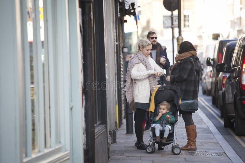 Dos mujeres con un cochecito con un bebé se colocan en el carril del ladrillo de la calle imagen de archivo libre de regalías