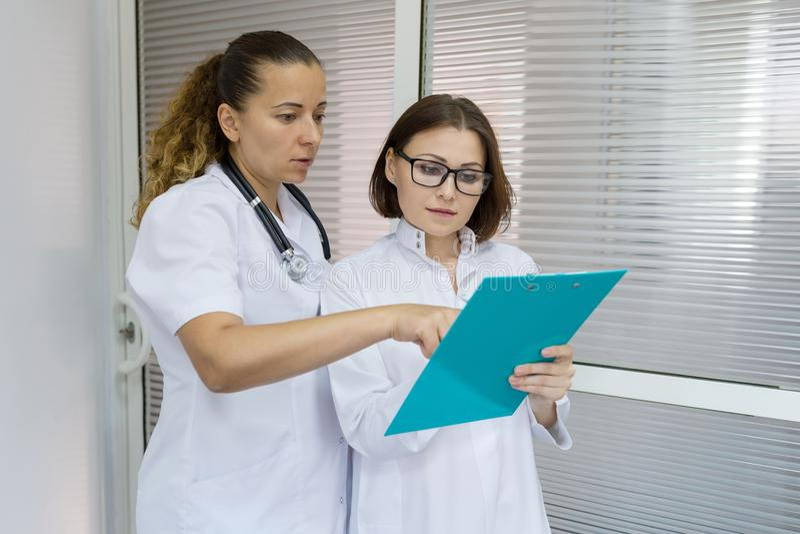 Dos mujeres cuidan y cuidan hablar en el hospital en el fondo de la puerta foto de archivo