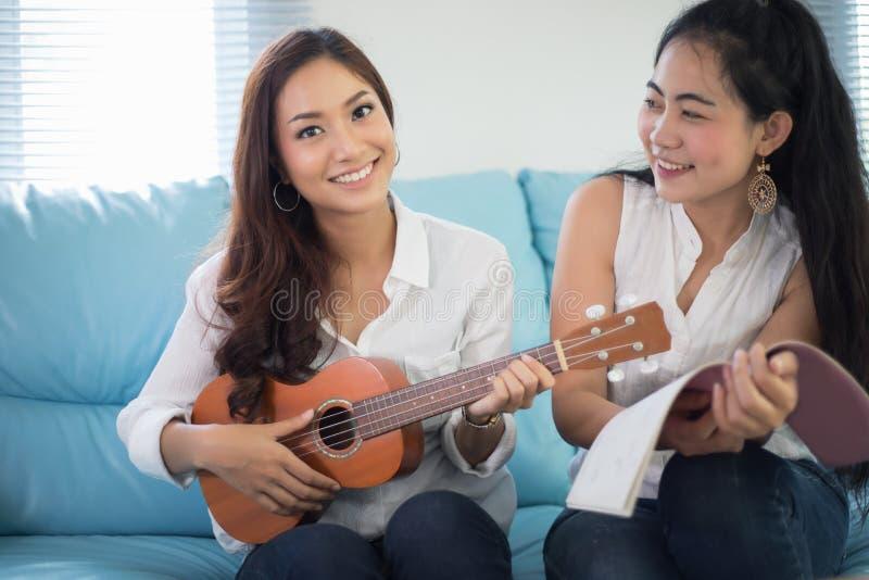 Dos mujeres de Asia se están divirtiendo que juega el ukelele y que sonríe en el hom fotografía de archivo