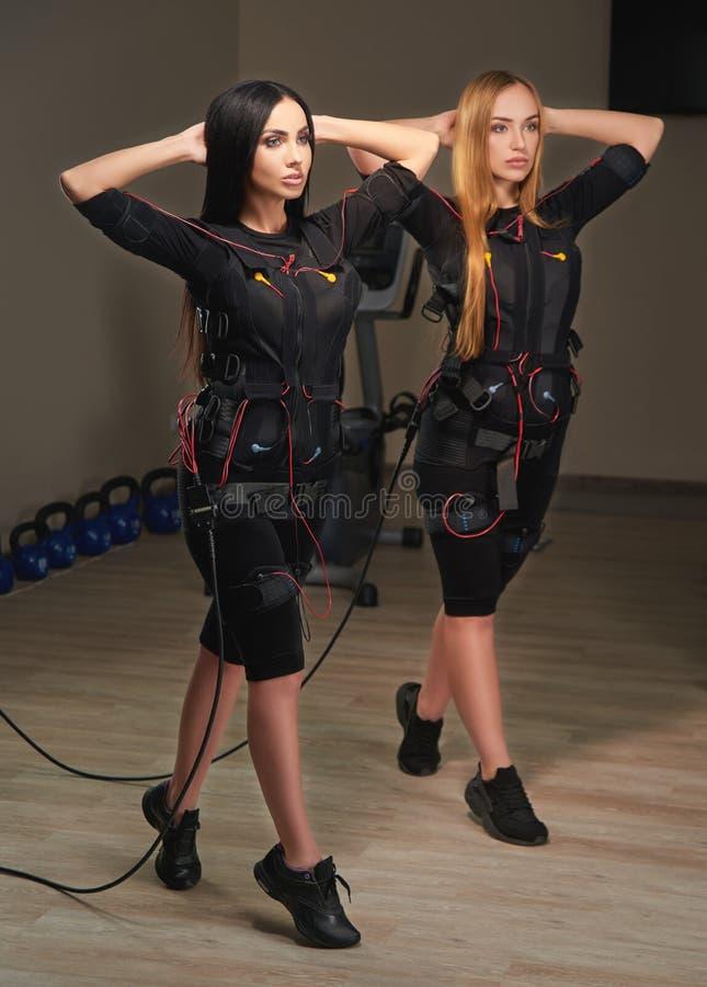 Dos mujeres de la aptitud del ccsme que hacen ejercicios de la estocada efecto del resplandor imagenes de archivo