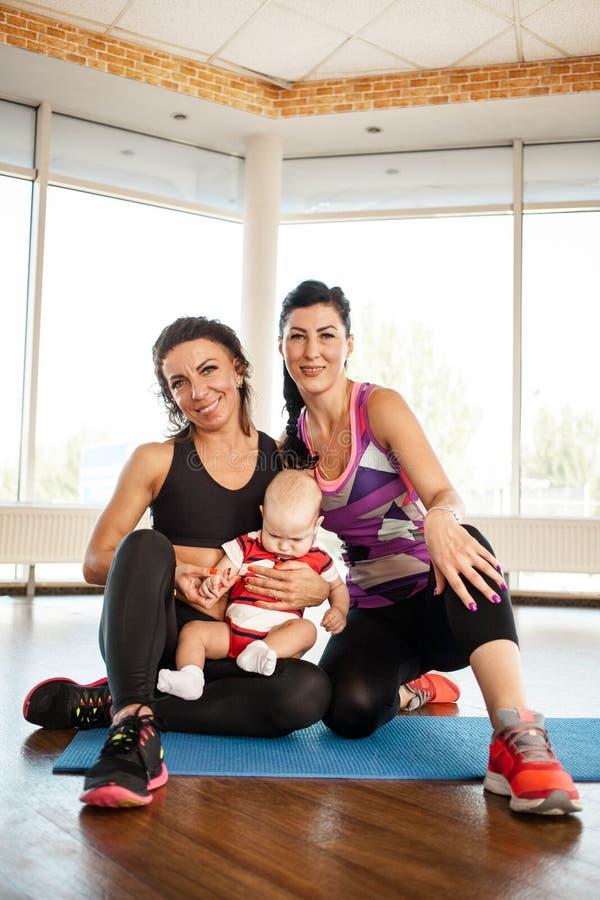 Dos mujeres de los deportes con un niño foto de archivo