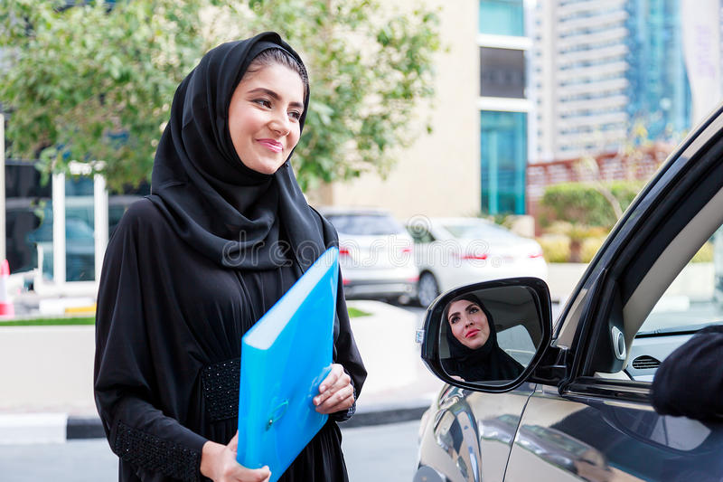 Dos mujeres de negocios árabes que discuten al lado de un coche fotos de archivo