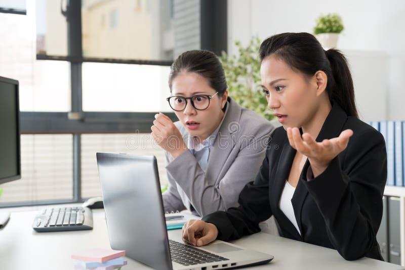 Dos mujeres de negocios asiáticas consiguieron el problema imagenes de archivo