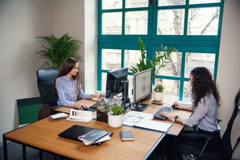 Dos mujeres de negocios caucásicas que mecanografían en el ordenador durante el trabajo en la oficina de arquitecto moderna fotos de archivo libres de regalías