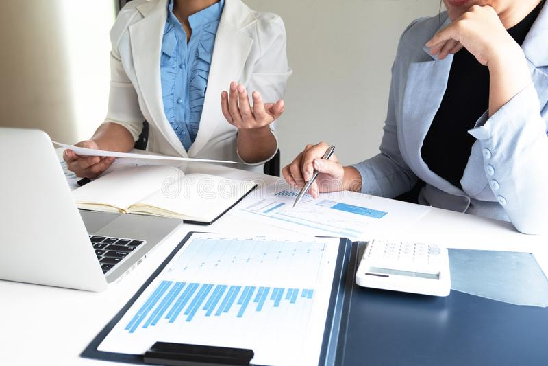 Dos mujeres de negocios del líder que discuten las cartas y los gráficos que muestran los resultados imágenes de archivo libres de regalías