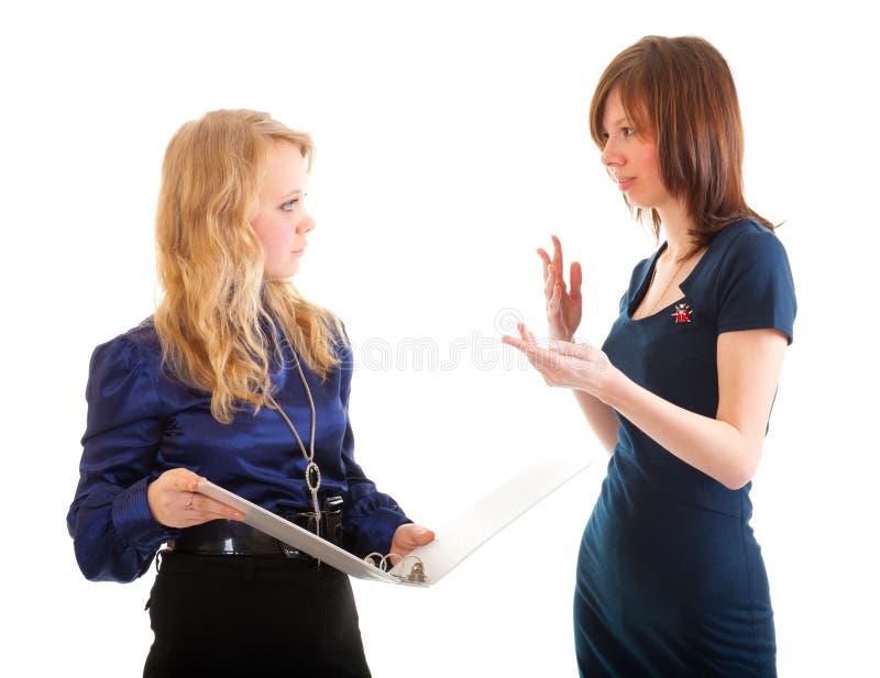Dos mujeres de negocios jovenes que discuten documentos fotos de archivo