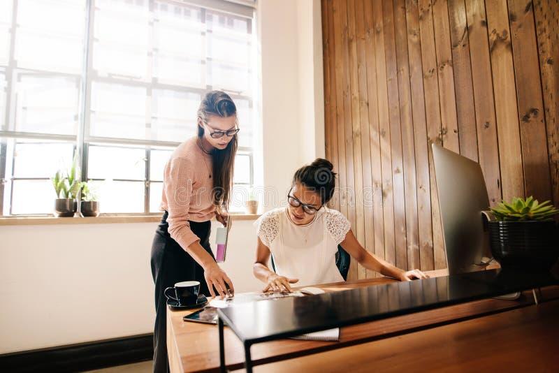 Dos mujeres de negocios que leen documentos en el escritorio imagenes de archivo