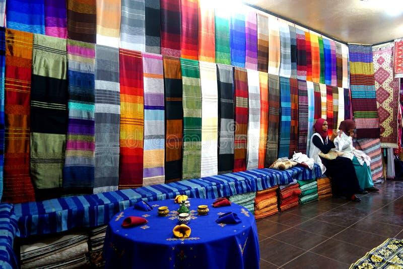 Dos mujeres del Berber están trabajando en telas coloridas del souk en Marruecos en Marruecos foto de archivo libre de regalías
