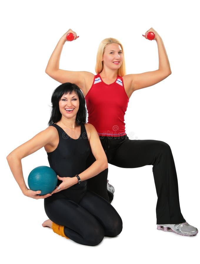 Dos mujeres del deporte con la bola y pesas de gimnasia imágenes de archivo libres de regalías