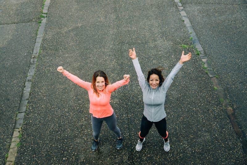 Dos mujeres deportivas acertadas que celebran metas del entrenamiento de la aptitud imagen de archivo libre de regalías