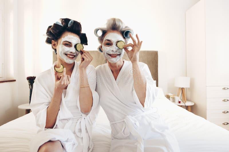 Dos mujeres en albornoces con el paquete de cara de la belleza que se sienta en cama foto de archivo libre de regalías
