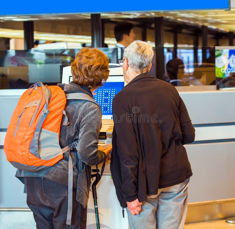 Dos mujeres en el mostrador en el aeropuerto, Tokio, Japón Visión posterior Con el foco selectivo fotografía de archivo libre de regalías