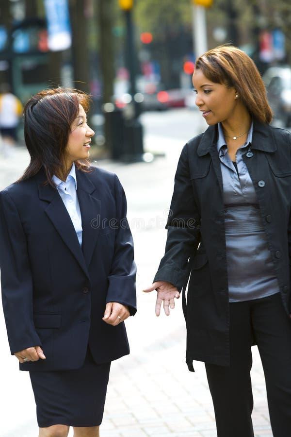 Dos mujeres en la acera de la ciudad fotos de archivo