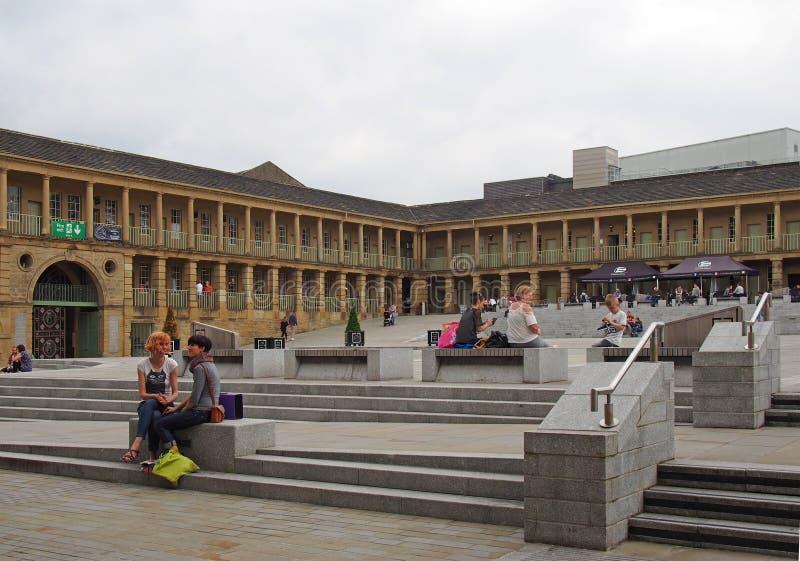 Dos mujeres en la conversación se sentaron en los pasos del pasillo del pedazo en Halifax West Yorkshire con compras de la gente  foto de archivo libre de regalías