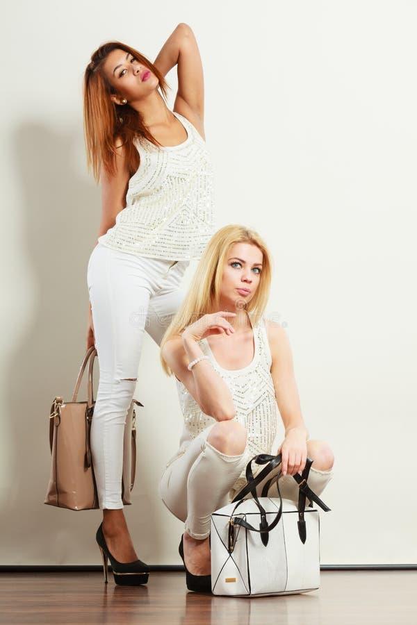 Dos mujeres en la ropa blanca con los bolsos de los bolsos fotos de archivo