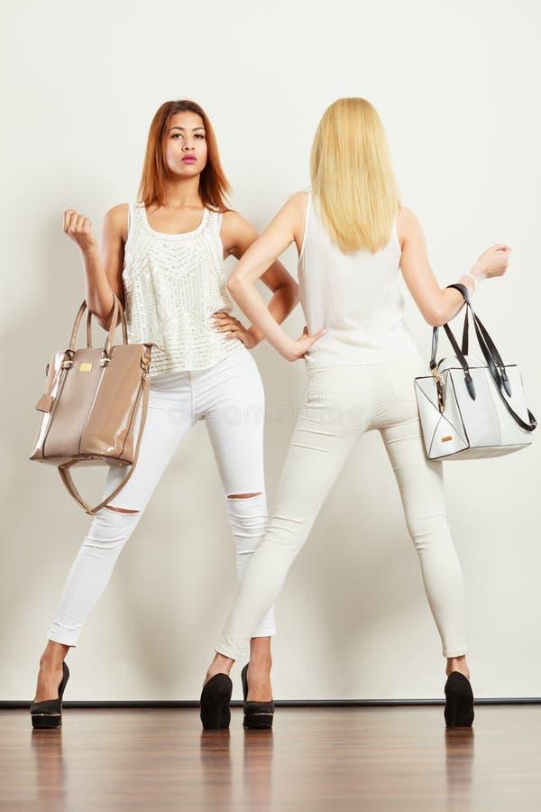Dos mujeres en la ropa blanca con los bolsos de los bolsos fotografía de archivo