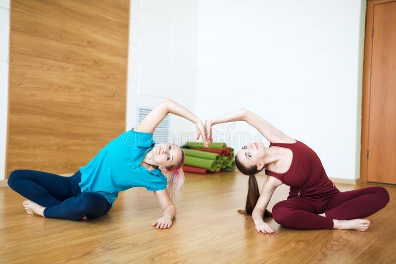 Dos mujeres en la ropa de deportes que hace estirar ejercitan en la estera de la yoga Concepto sano de la vida y de la aptitud imagen de archivo