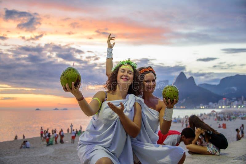 Dos mujeres en los trajes de las diosas griegas en el fondo del ocaso hermoso en Ipanema varan, Carnaval imágenes de archivo libres de regalías