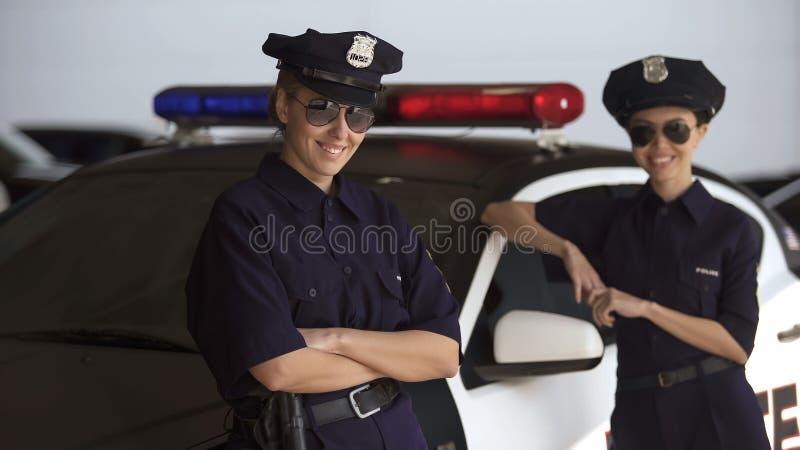Dos mujeres en los uniformes de la policía que se colocan cerca del coche patrulla y que sonríen, ley y orden imagenes de archivo