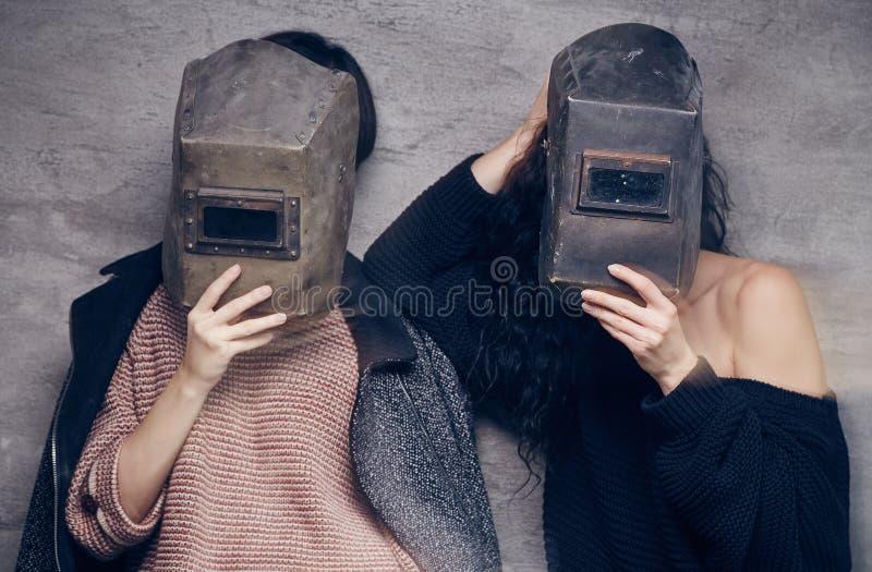 Dos mujeres en máscaras de un soldador imagenes de archivo