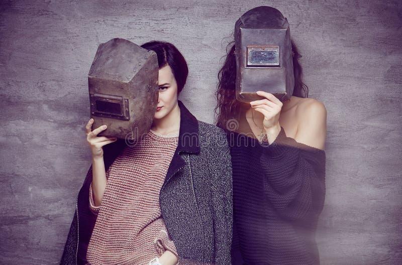 Dos mujeres en máscaras de un soldador foto de archivo