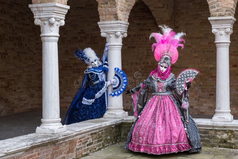 Dos mujeres en máscaras y trajes en el carnaval de Venecia imagenes de archivo