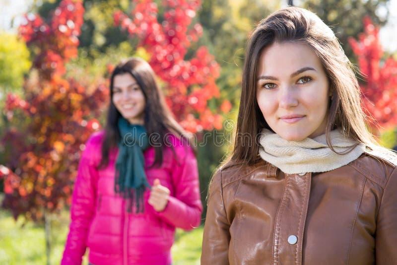 Dos mujeres en parque del otoño imagenes de archivo
