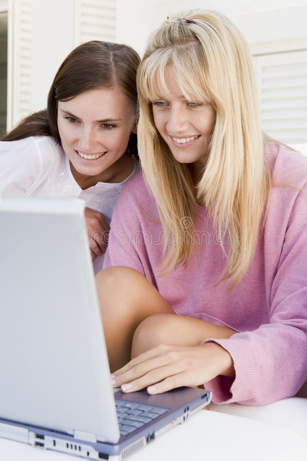 Dos mujeres en patio usando la computadora portátil foto de archivo libre de regalías