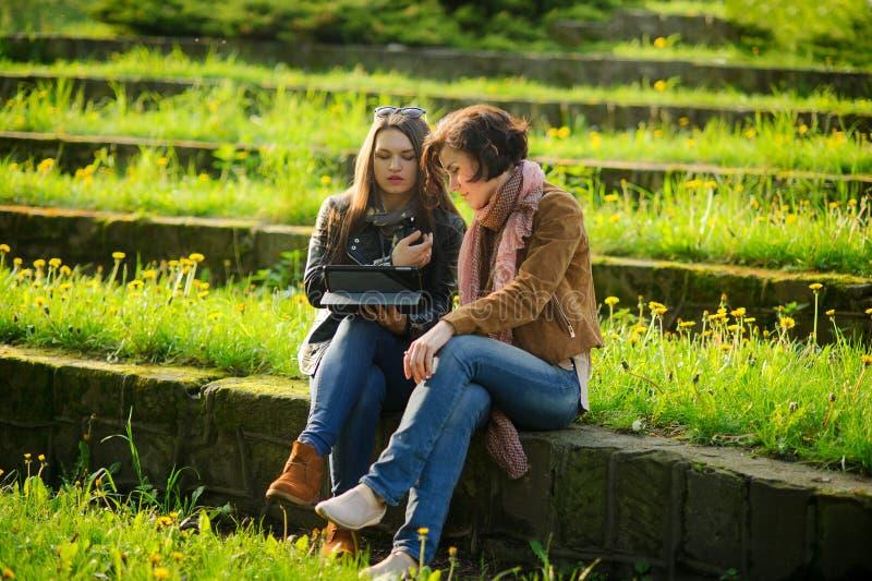 Dos mujeres encantadoras jovenes se sientan en los pasos de piedra con la tableta en manos foto de archivo libre de regalías