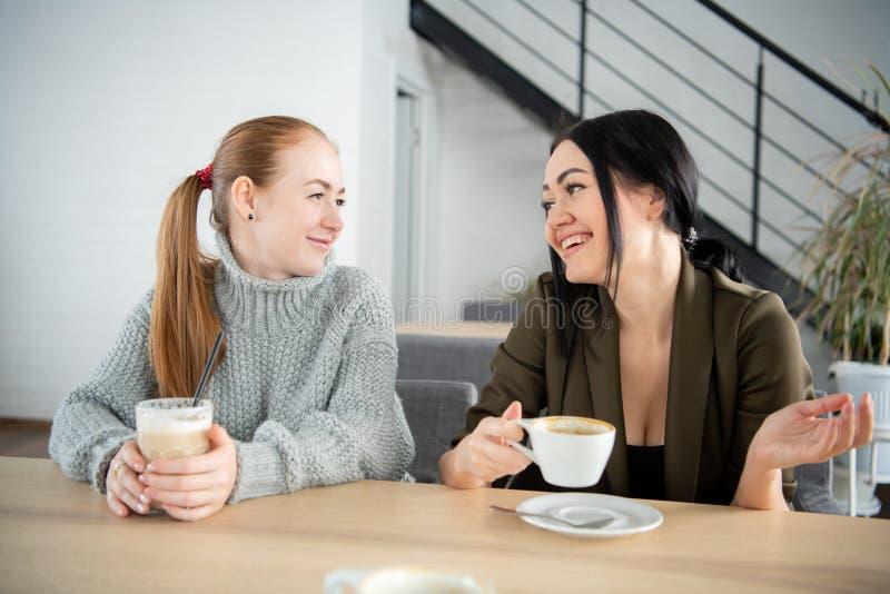 Dos mujeres están sosteniendo la taza de café El sentarse en el sofá que habla del trabajo por la mañana Una taza de café hará imagen de archivo libre de regalías