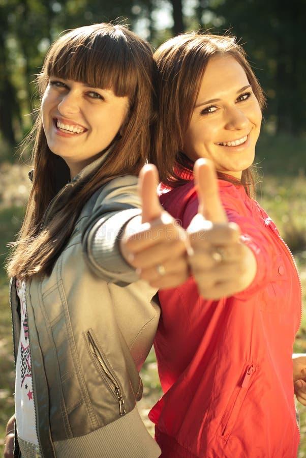 Dos mujeres felices con los pulgares para arriba foto de archivo libre de regalías