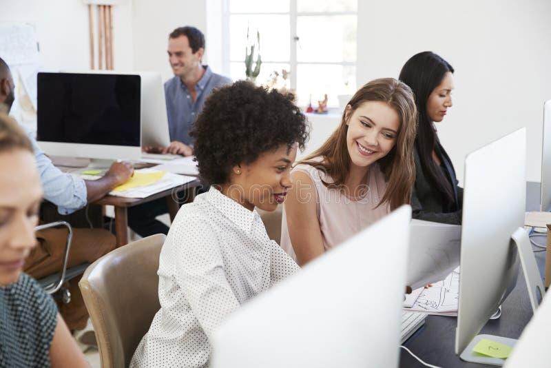 Dos mujeres felices discuten el trabajo en el ordenador en oficina abierta del plan imagen de archivo libre de regalías