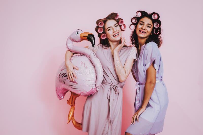 Dos mujeres felices en albornoces en fondo rosado imagenes de archivo