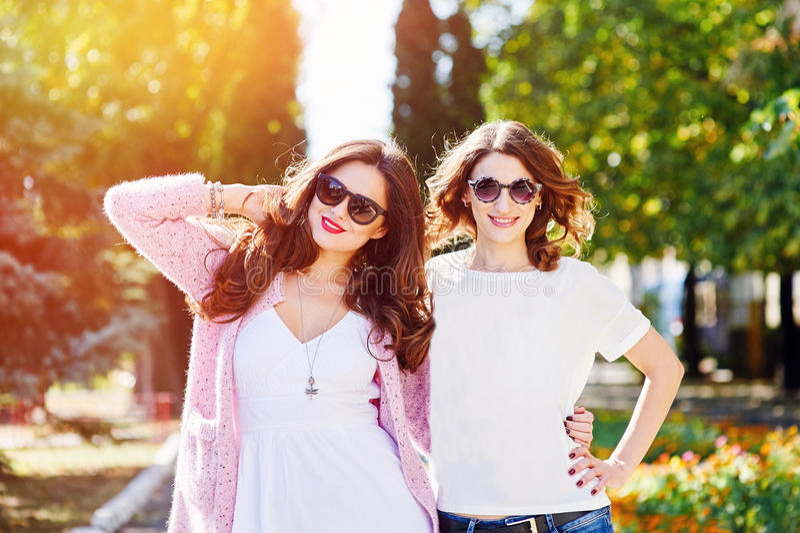 Dos mujeres felices jovenes que caminan en la ciudad del verano fotos de archivo