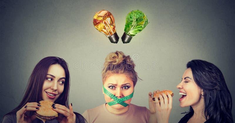 Dos mujeres felices que comen las hamburguesas que miran a la muchacha rechoncha subrayada con la cinta métrica alrededor de su b imagen de archivo libre de regalías