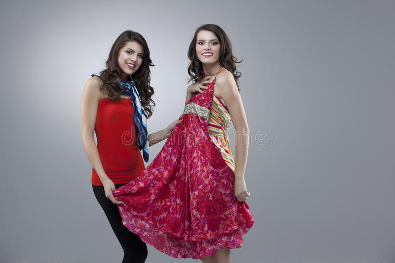 Dos mujeres felices que intentan la alineada roja de la flor fotos de archivo libres de regalías
