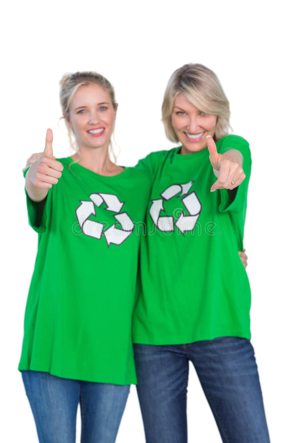 Dos mujeres felices que llevan las camisetas de reciclaje verdes que dan los pulgares para arriba imagen de archivo